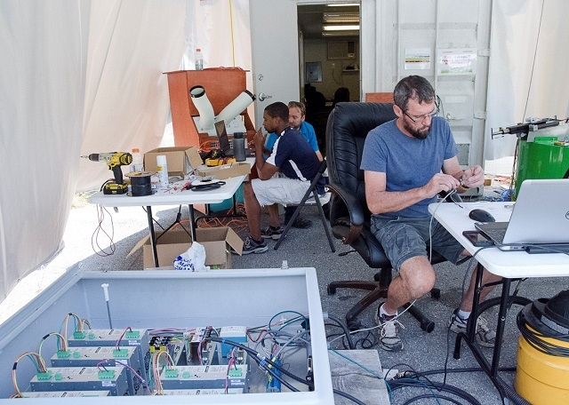 Shows people working on pieces of equipment